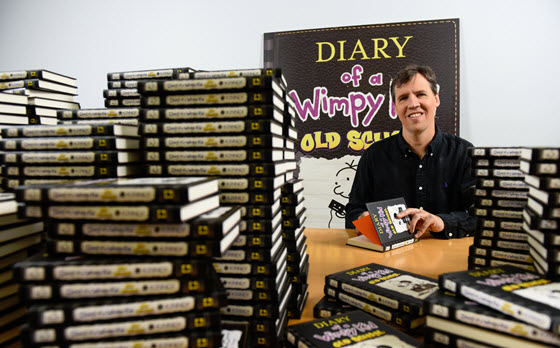 Jeff Kinney signing stacks of books